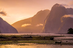 Milford Sound at sunset after a storm. After a storm, the sun breaks through the clouds to softly light the fjords of Milford Sound in South Island, New Zealand Royalty Free Stock Photos