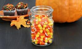 Milho de doces em um frasco de pedreiro rústico Abóbora e queques no b Imagens de Stock Royalty Free