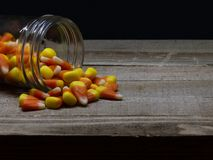 Milho de doces que derrama fora de um frasco de vidro em uma tabela de madeira foto de stock