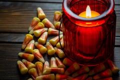 Milho de doces um deleite de Dia das Bruxas em uma tabela de madeira com um castiçal de vidro vermelho que faz os incandescer na  foto de stock royalty free