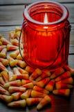 Milho de doces um deleite de Dia das Bruxas em uma tabela de madeira com um castiçal de vidro vermelho que faz os incandescer na  imagens de stock