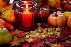 Milho de doces um deleite de Dia das Bruxas em uma tabela de madeira com um castiçal de vidro vermelho que faz os incandescer na  fotografia de stock