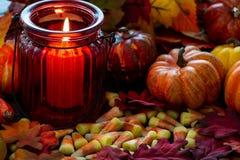Milho de doces um deleite de Dia das Bruxas em uma tabela de madeira com um castiçal de vidro vermelho que faz os incandescer na  imagem de stock royalty free