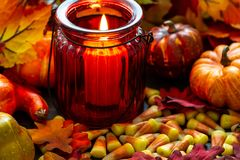 Milho de doces um deleite de Dia das Bruxas em uma tabela de madeira com um castiçal de vidro vermelho que faz os incandescer na  imagem de stock