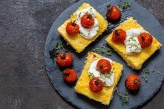Milho do Polenta com tomates e queijo creme cozidos foto de stock royalty free