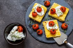 Milho do Polenta com tomates e queijo creme cozidos fotografia de stock royalty free