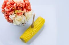 Milho doce fervido dourado na terra branca com flowe colorido Foto de Stock
