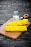 Milho e sal em uma tabela de madeira Imagem de Stock