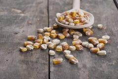 Milho em uma colher de madeira Imagem de Stock Royalty Free