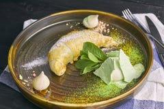 Milhojas de manzana cocido con una cucharada del helado de vainilla y del merengue en una tabla de madera oscura, primer postre d foto de archivo libre de regalías