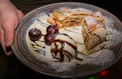 Milhojas y helado en una placa en las manos del primer del camarero imagen de archivo libre de regalías