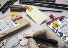 Milicyjny ekspert pisze o etykietka dowodu liczbie, Różnorodny laboranckich testów sądowy wyposażenie obraz stock