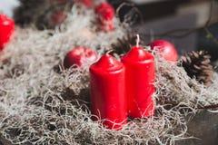 Milieux de Noël - cône rouge de bougie, de pomme et de pin Photo stock