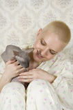 Miling bald woman with cat Stock Photo