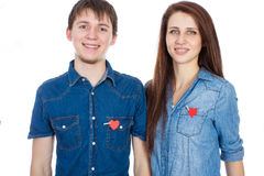 Miling couple standing isolated on white background with paper heart in pocket. Stock Image