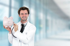 Miling doctor holding listening to piggy bank with stethoscope Stock Image