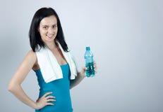 Miling junge Frau, die eine Wasserflasche anhält Lizenzfreie Stockbilder