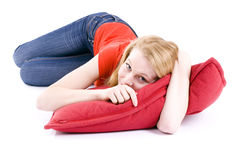 Miling  young woman lying on the red pillow Royalty Free Stock Photo