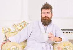 Milioner cieszy się ranek kawę Faceta obsiadanie w pięknym krześle nad białym tłem Mężczyzna marszczy brwi jego i podnosi zdjęcia stock