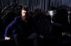 Milioner w eleganckim kostiumu siedzi na luksusowej kanapie zdjęcie stock