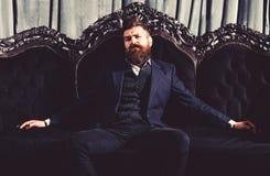 Milioner w eleganckim kostiumu siedzi na luksusowej kanapie Brodaty mężczyzna z ufną twarzą w klasycznym wnętrzu luz zdjęcie royalty free