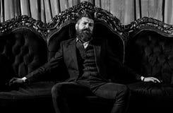 Milioner w eleganckim kostiumu siedzi na luksusowej kanapie Brodaty mężczyzna z ufną twarzą w klasycznym wnętrzu luz obraz stock