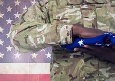 Militär hållande amerikanska flaggan mot amerikanska flaggan Royaltyfria Bilder
