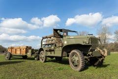 Militär jeep som drar släpet som bär träaskar med kulor Royaltyfri Bild