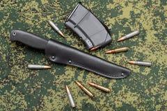 Militär kniv i svart läderskida, tidskrift och kassetter på kamouflagebackround Royaltyfria Bilder