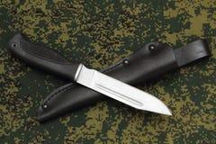 Militär kniv som ligger över den svarta läderskidan på kamouflagebakgrund Royaltyfri Bild