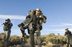 Militär man som bär en sårad kvinnlig Solider Arkivfoton
