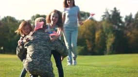 Militär man som kramar två döttrar stock video