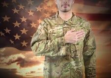 Militär mit der Hand auf seinem Herzen gegen Sonnenuntergang und amerikanische Flagge Stockfoto
