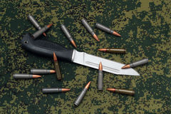 Militär sheathless kniv och kassetter på kamouflagebackround Royaltyfri Foto