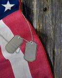 Militära hundetiketter på amerikanska flaggan Arkivfoton