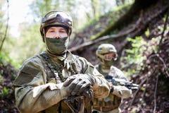 Militära män i hjälm och kamouflage royaltyfria foton