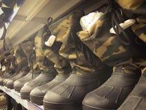 Militära mäns gummistöveler, skor i kaki- toat för skyddande färger i rad på hyllan i lagret, shoppar arkivfoto