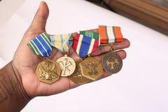 Militära medaljer i en hand Royaltyfri Fotografi