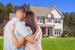 Militära par som ser det trevliga nya huset Arkivfoto