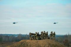 Militärarmeehubschrauber, die über Militärfeld fliegen stockbild