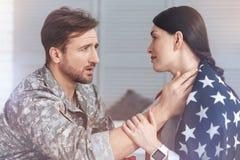 Militärehemann, der die besorgte Frau bedeckt in USA-Flagge tröstet Stockbilder