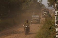 Militärfordon som passerar på en grusväg Arkivfoton