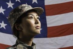 Militärfrau vor US-Flagge, vertikale Militärfrau vor US-Flagge, horizontal Stockfotografie