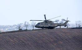Militärhubschrauber im Flug über Ackerland Großbritannien Lizenzfreie Stockfotos