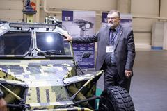Militärischer gepanzerter Buggy der ukrainischen Produktion mit dem Entwickler an der Ausstellung stockfotografie