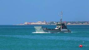 Militärlandungsboot schwimmt schnell auf die blaue Oberfläche von Meer Spuren des Schaums auf Hintergrund des Ufers hinterlassend stock footage