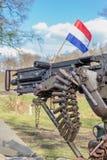 Militärmaschinengewehr mit Kugeln und niederländischer Flagge Lizenzfreies Stockbild