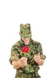 Militäroffizier, der das Blumenlächeln schüchtern mit dem Kopf gebeugt hält Lizenzfreies Stockfoto