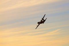 Militärt flygplan i de gula skyesna Arkivfoton