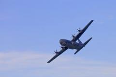 Militärt flygplan i skyesna Arkivfoto